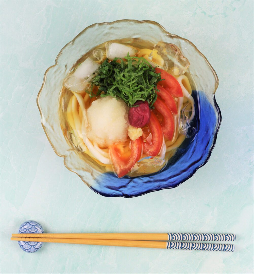 A bowl of cold udon topping with tomato, daikon oroshi (grated daikon radish), shiso, and umeboshi (pickled plum)