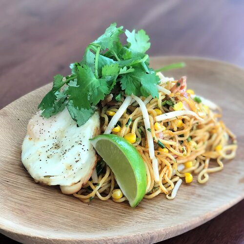 Yakisoba with sauce using a blend of spicy sriracha, soy sauce, and tonkatsu sauce topping with cooked egg, cilantro, lime wedge, and sesame seeds