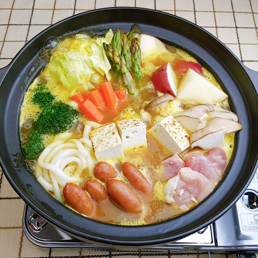Curry hotpot cook with jumbo udon noodles only with chicken thigh, mini sausages, grilled tofu, cabbage, potatoes, eringi mushrooms, carrot, broccoli, and asparagus