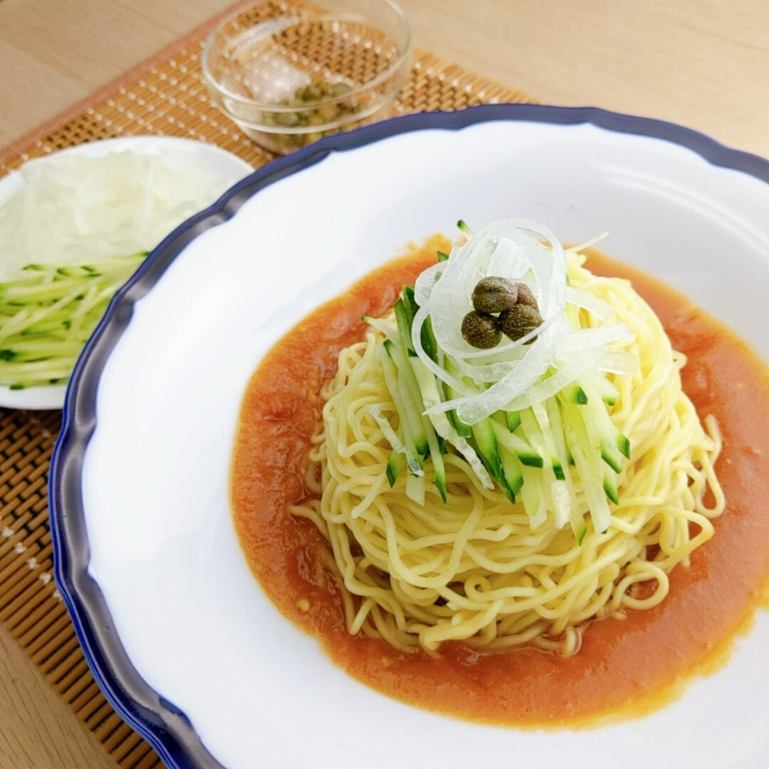 Hiyashi Chuka with tomato sauce topped with cucumber, onions, and capers
